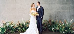 Bride and groom looking lovingly on at each other, surrounded by altar greenery
