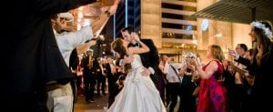 Bride and groom kissing as they exit the wedding to sparklers held by cheering guests in two lines