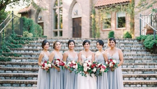 Bridesmaids in pale gray standing with the bride on her wedding day, holding their bouquets in front of stone stairs