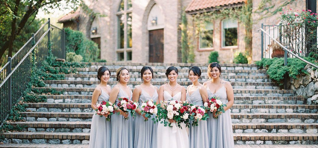 Bridesmaids in pale gray standing with the bride on her wedding day holding their bouquets in front of stone stairs