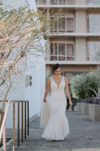 Bride walking in her white gown, from the hotel