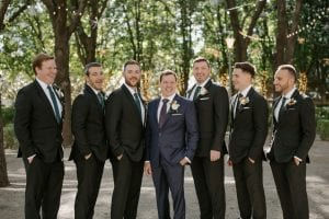 Groom and his groomsmen smiling in a garden while waiting for the wedding ceremony at Marie Gabrielle