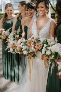 Bride and her bridesmaids, on their way to the ceremony, laughing and carrying their bouquets. The bridesmaids are in emerald green