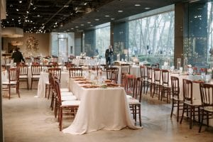 A wedding reception setup at Marie Gabrielle with white linens and brown bistro chairs. There are brown charger plates and rust napkins on the table settings, with glassware