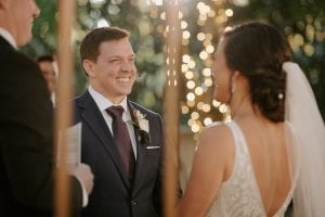 Groom and bride smiling at each other at the altar, as the officiant looks on at the garden setting