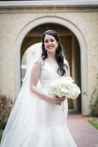 Smiling bride looking radiant in a white gown on her wedding day holding a bouquet of flowers with a rosary tied to the bouquet