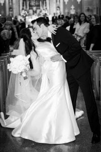 Bride and groom kissing as they exit the chapel and guests look on