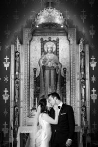 Bride and groom kissing in front of a picture of Christ