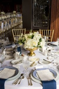 Table with plateware, serveware and glassware, set with a white centerpiece, blue napkins, menus and patterned plates for the dinner reception