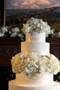 Closeup of a white, four tier wedding cake decorated with hydrangea and roses, with a monogram on the second tier from the bottom