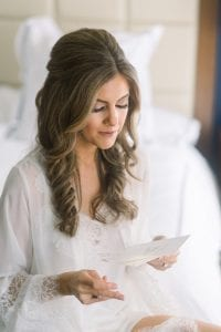 Bride wearing a white lace robe reading a letter in a hotel bed on her wedding day