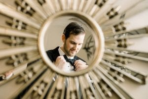 Groom looking at his reflection in a gold sunburst mirror as he fixes his black bowtie on his wedding day