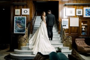 Bride on her wedding day, standing with her groom by her side in a black suit on the stairs of The Adolphus hotel in Dallas, wearing a low backed white wedding gown with a massive white bow tied at her waist, and long, flowing train cascading on the carpet