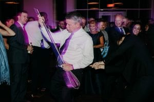 Father of the bride dancing with a giant whisk on the dance floor as guests look on and laugh in the background