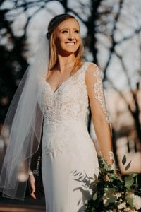 Bride smiling into the distance in her wedding gown and veil holding her bridal bouquet
