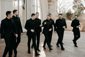 Groom and his groomsmen laughing and walking as the groom gives another groomsman a fist bump