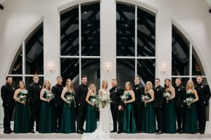 Bride groom their bridesmaids and groomsmen smiling at the camera while posing in the chapel