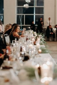 Head table filled with glassware as the wedding party sits and eats