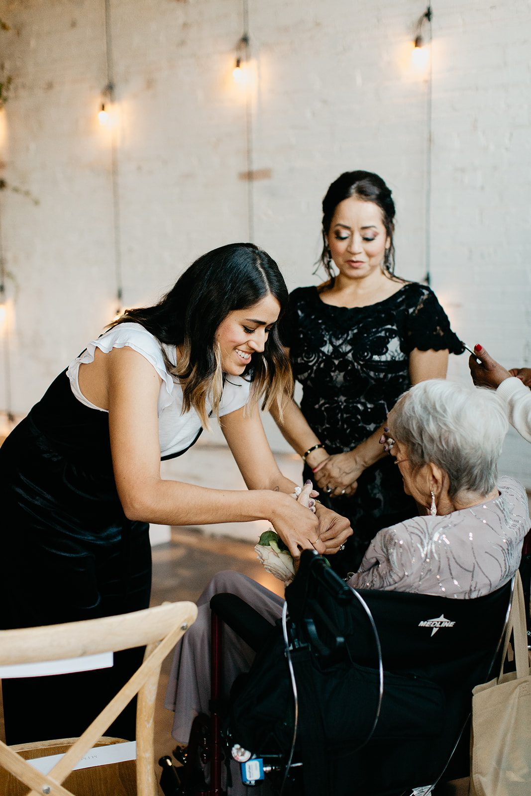 Planner helping a grandmother put on a wrist corsage before the wedding ceremony