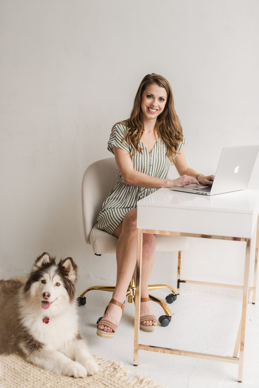 Smiling woman sitting on an ivory rolling office chair typing on a macbook air on a sleek white desk while a brown and white Siberian Husky sits by her side