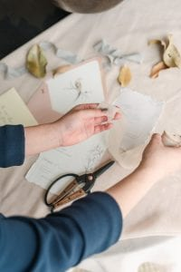 Hands holding silk ribbon over a stationery suite