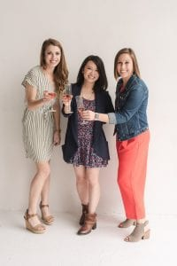 Three smiling women toasting with champagne flutes