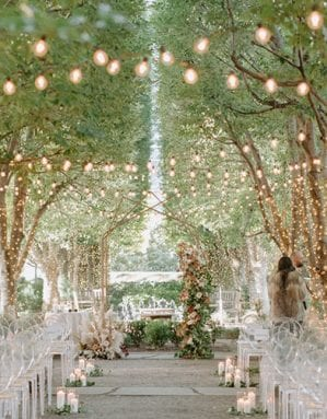 Set up of a wedding ceremony at Marie Gabrielle with clear acrylic ghost chairs within a grove of trees, with string lights hanging and more lights wrapped around the base of each tree, with a floral arch in the front