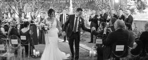 Bride and groom smiling as they exit their wedding ceremony while bridal party and guests look on and the groom shakes the hand of a guest