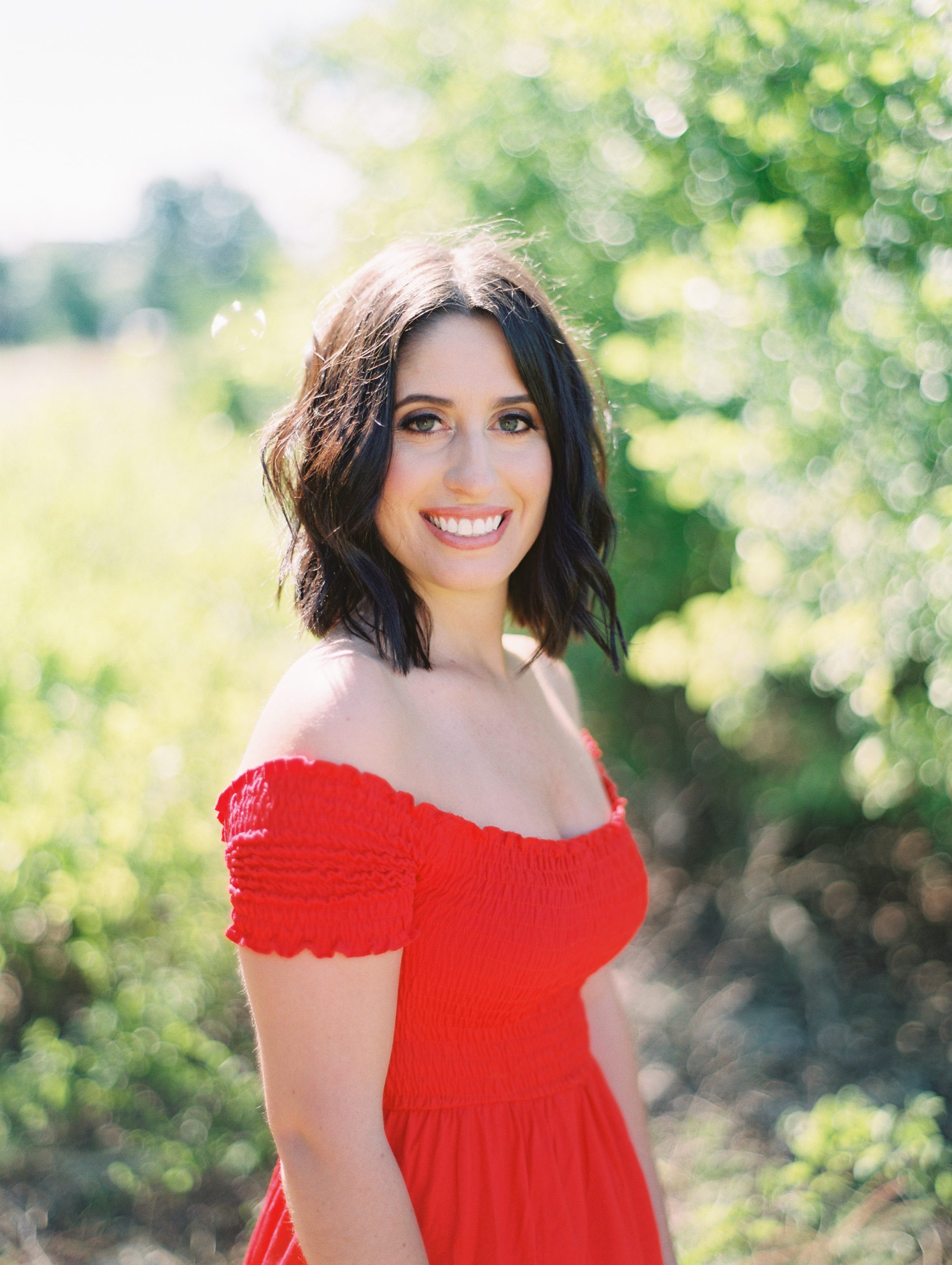 Smiling headshot of a brunette with brown eyes standing in front of a green backdrop wearing an off shoulder red dress