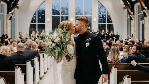 Bride and groom kissing as they walk out the chapel affer their ceremony and bride is holding her bouquet as guests look on