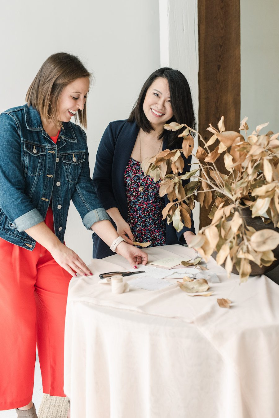 Two smiling women arranging a stationery suite hovering over a table with blush linen