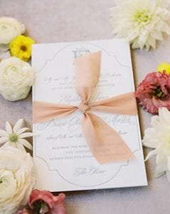 Wedding stationery suite with gray calligraphy script on it, surrounded by real flowers around it, tied with blush ribbon and a gold wax seal