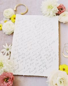 Handtorn paper with black calligraphy script on it, with real flowers around it