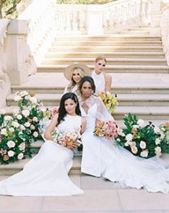 Four women sitting on a grand stone staircase, holding bouquets with clusters of greenery by them