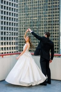 Groom twirling his bride on a rooftop with a skyscraper in the background
