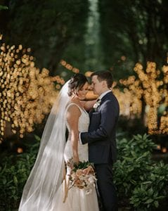 Bride and groom holding each other and smiling at the camera, in a grove of lighted trees behind them