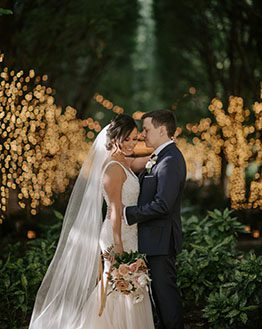 Bride and groom holding each other and smiling at the camera in a grove of lighted trees behind them