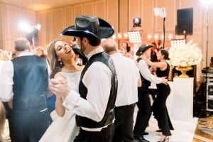 Bride and her groom on the dance floor as he wears a black cowboy hat, with other dancing guests in the background