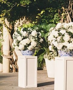 Two large white and green floral arrangements in ginger jars