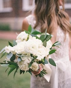 Bride holding her all white bridal bouquet