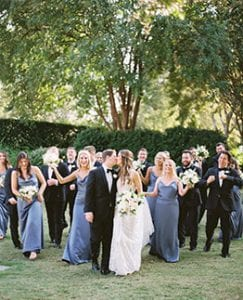 bride and groom kiss each other while their bridal party walks behind them cheering and laughing