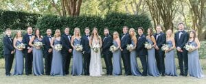 Bride, groom and their bridal party looking dashing. Bridesmaids are in dusty blue and the groomsmen are in black suits, smiling in a garden