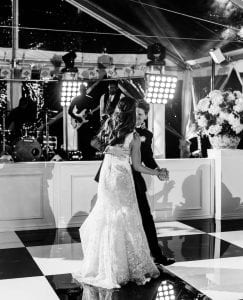 Bride and groom having their first dance on a black and white checkered dance floor while the band sings in the background